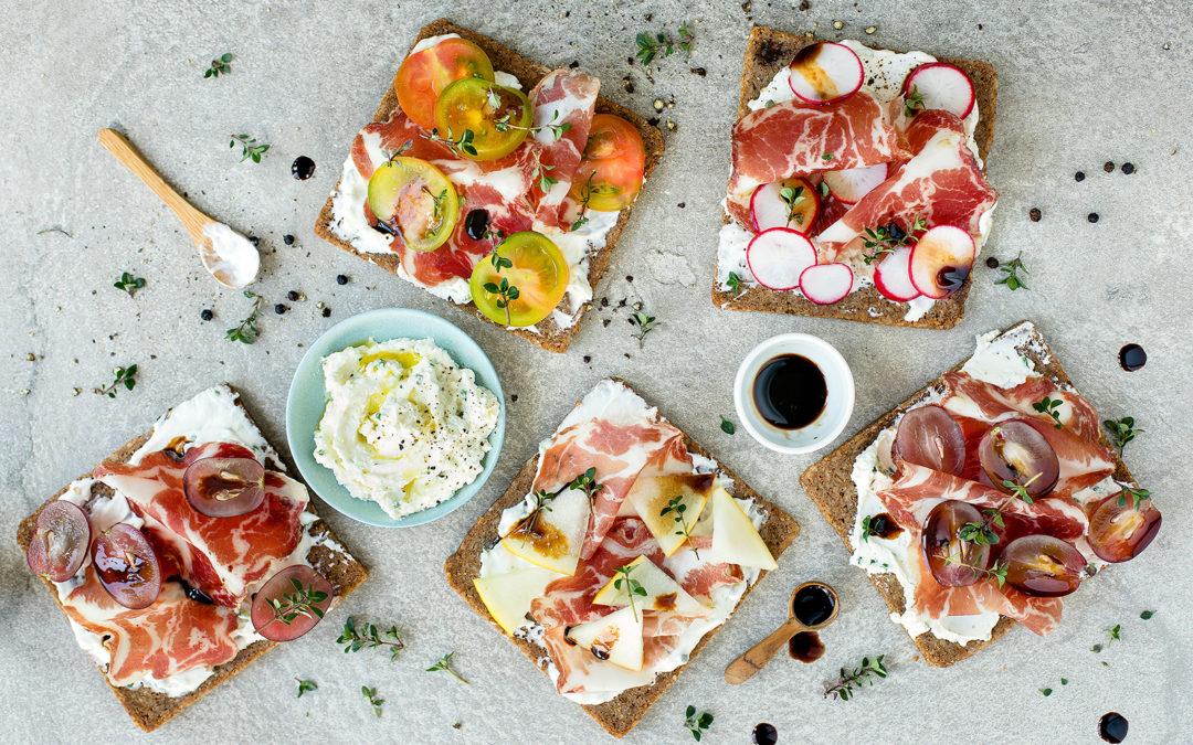 Crostini di pane nero con caprino aromatizzato, frutta, verdura e Coppa di Parma IGP